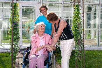 Caregiver smiling on two elderly women talking
