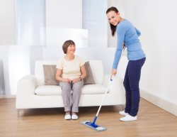 caretaker cleaning floor with mop while senior women sitting on sofa