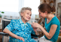 caregiver giving medication to an elderly woman in wheelchair